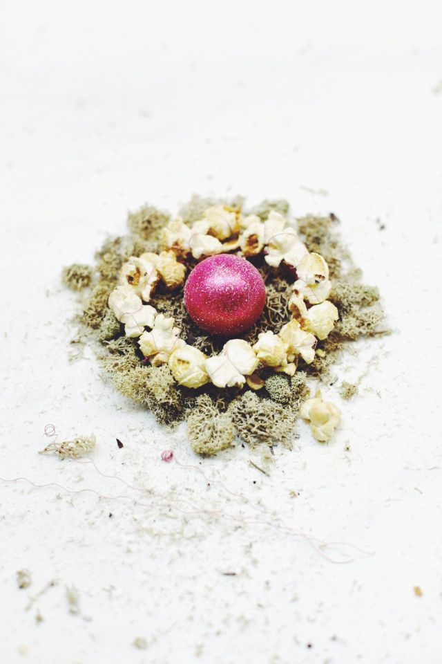 Christmas wreath made of a pink christmas bauble, popcorn and pink wire: food photography via Stilzitat
