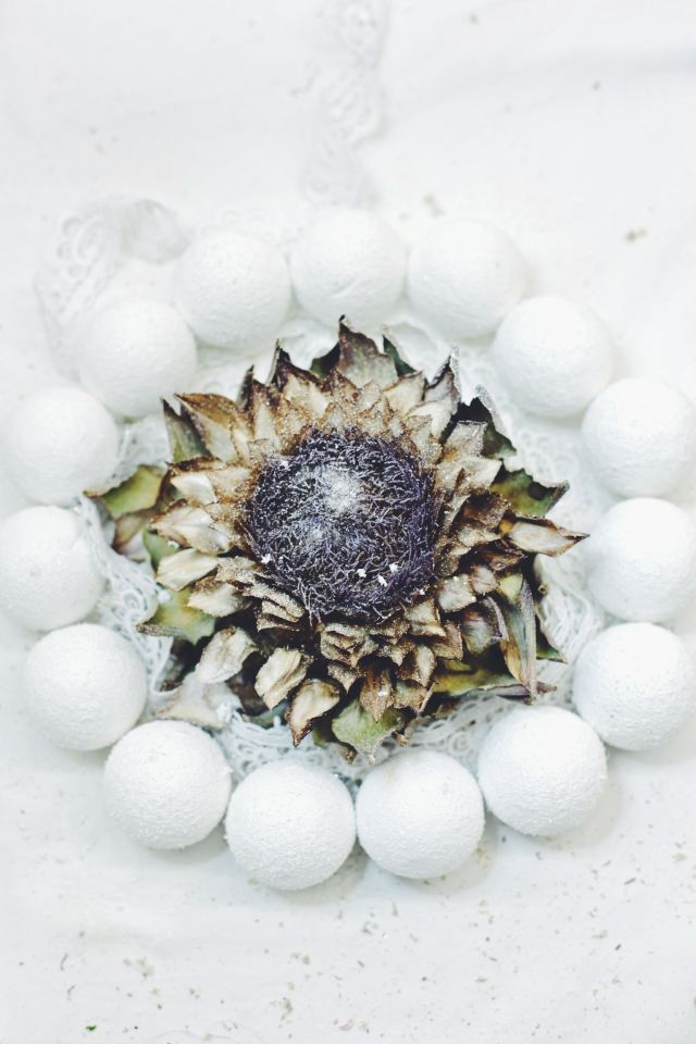 Christmas wreath made of white christmas baubles and dried artichoke food photography via Stilzitat